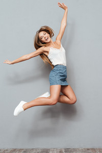Cheerful pretty young girl jumping isolated on gray background