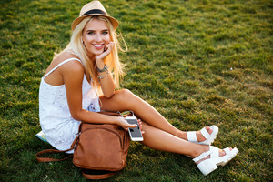 Cheerful pretty young woman in hat with backpack sitting on grass in summer