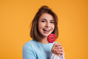 Cheerful pretty young woman laughing and eating lollipop over yellow background