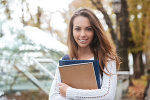Cheerful pretty young woman standing and holding notebooks in park