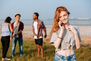 Cheerful redhead young woman talking on cell phone standing near her friends outdoors
