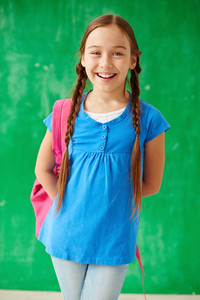 Cheerful schoolgirl with backpack looking at camera
