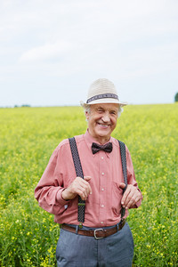 Cheerful senior man looking at camera on background of field or meadow