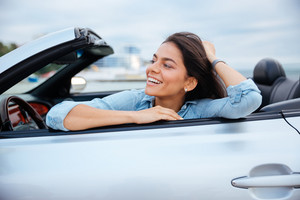 Cheerful smiling brunette woman resting in her cabriolet parked on the beach