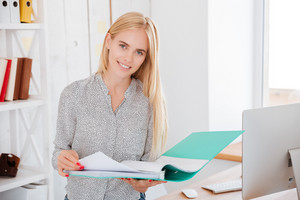 Cheerful smiling businesswoman standing and holding folder at the office and looking at camera