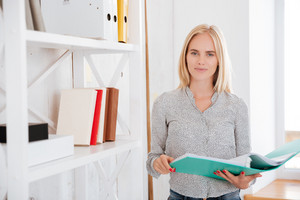 Cheerful smiling businesswoman standing and holding folder at the office