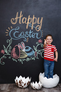 Cheerful smiling little boy showing thumbs up gesture while standing inside big cracked eggshell over chalk board with easter doodles background