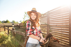 Cheerful smiling redhead cowgirl preparing horse saddle for a ride