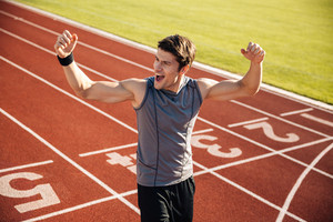 Cheerful sportsman celebrating his victory at a stadium