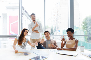 Cheerful successful multiethnic group of young business people showing thumbs up in office