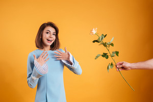Cheerful surprised young woman receiving pink rose over yellow background