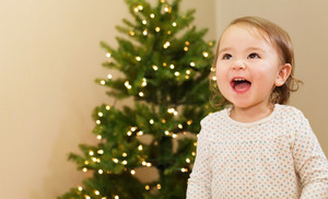 Cheerful toddler girl smiling in front of the Christmas tree
