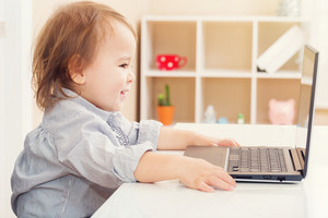 Cheerful toddler girl smiling while using her laptop in her house