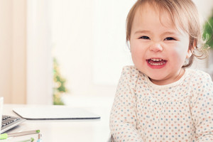 Cheerful toddler girl with a huge smile sitting at a desk in her house