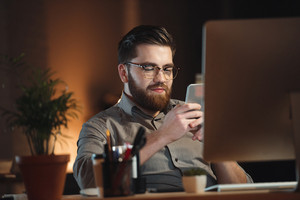 Cheerful web designer dressed in shirt and wearing eyeglasses working late at night and chatting by phone.