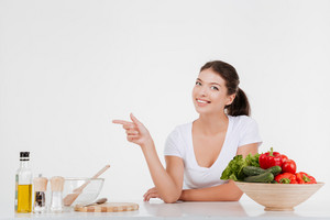 Cheerful woman cooking with vegetables while pointing left. Isolated on white background.