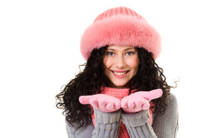 Cheerful woman in pink winter fur cap looking at camera with smile
