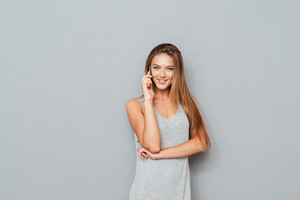 Cheerful woman talking on the phone isolated on a grey background