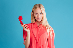 Cheerful woman talking on the phone tube and looking at camera isolated on a blue background