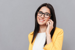 Cheerful woman wearing eyeglasses and dressed in yellow jacket talking by her phone over grey background. Look at camera.