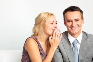 Cheerful woman whispering something funny in her husband's ear