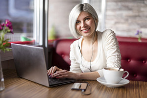 Cheerful woman working with laptop computer in cafe