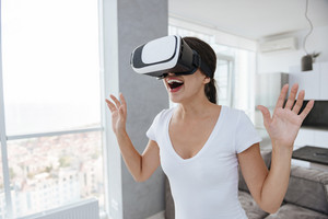 Cheerful yougn woman playing video games with virtual reality googles at home
