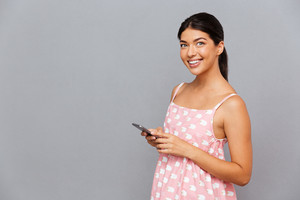 Cheerful young brunette woman in pink dress holding mobile phone isolated on a gray background