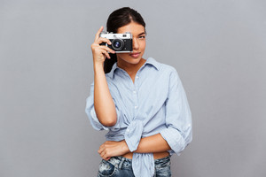 Cheerful young brunette woman making photo with camera isolated on a gray background