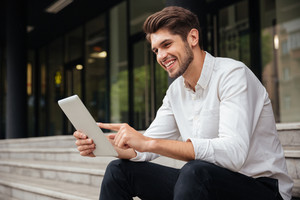 Cheerful young businessman sitting on stairs and using tablet outdoors