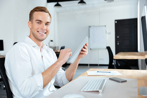Cheerful young businessman smiling and using tablet at the table
