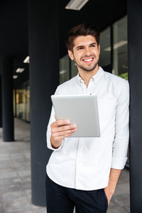 Cheerful young businessman standing and using tablet outdoors