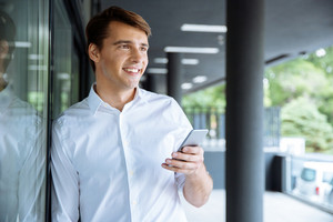 Cheerful young businessman waiting and using cell phone