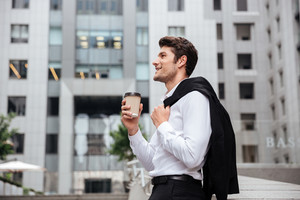 Cheerful young businessman walking and drinking coffee in the city