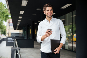 Cheerful young businessman with smartphone and documents walking outdoors