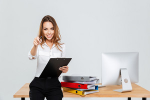 Cheerful young businesswoman holding folder and pointing pen at camera at the office