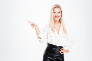 Cheerful young businesswoman pointing finger away at copyspace isolated on white background