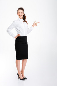 Cheerful young businesswoman pointing finger away over white background