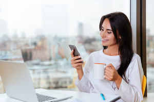 Cheerful young businesswoman with laptop sitting and using mobile phone in office
