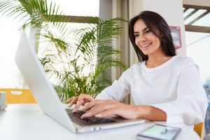 Cheerful young businesswoman working with laptop and mobile phone in office