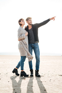 Cheerful young casual couple standing at the seashore in autumn and pointing away