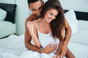 Cheerful young couple hugging and laughing in bed at home