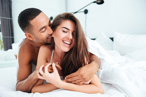 Cheerful young couple lying and embracing in bed at home