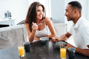 Cheerful young couple smiling and having breakfast on the kitchen at home