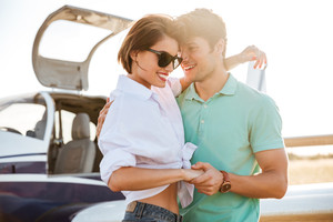 Cheerful young couple standing and hugging near private airplane