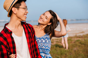 Cheerful young couple standing and hugging outdoors