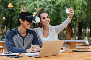 Cheerful young couple using virtual reality glasses and making selfie with smartphone outdoors