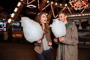 Cheerful young couple with cotton candy standing and laughing in amusement park