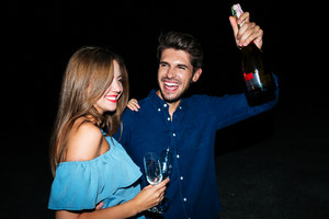 Cheerful young couple with glasses and bottle of champagne having fun at night on the beach