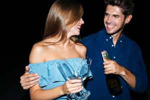 Cheerful young couple with glasses and bottle of champagne hugging at night
